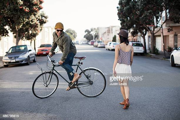 Guy riding circles around girl on bicycle