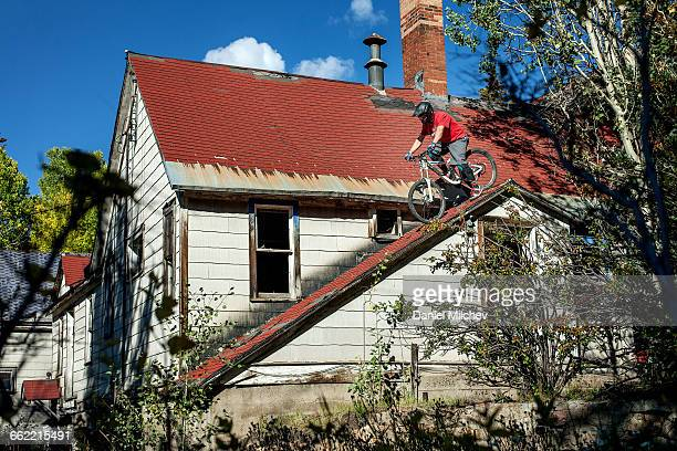 Guy riding his mountain bike on a rooftop.