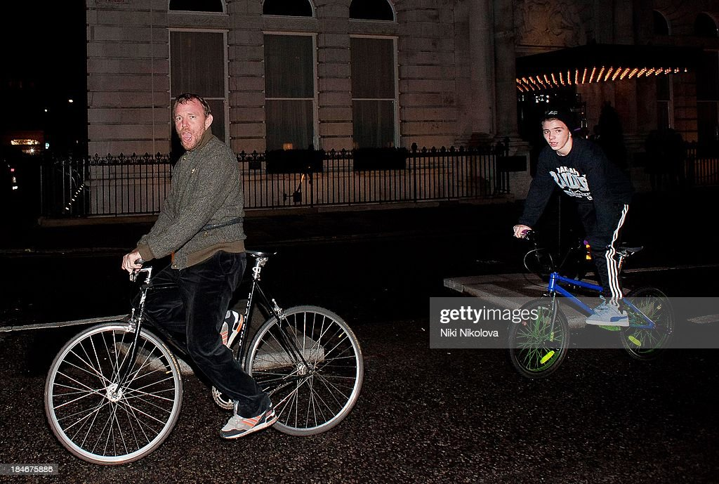 Guy Ritchie and son Rocco Ritchie (R) sighted on bicycles on October 14, 2013 in London, England.