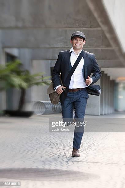 Guy running down city sidewalk with shoulder bag