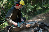 Guy in full green overall working with an electric chainsaw cutting into log. Shallow focus, sawdust flying around work area. Some cut up logs can be seen near work area. Guy has red ear mufflers and