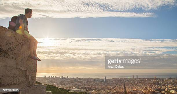 Guy sitting with the Barcelona city views.