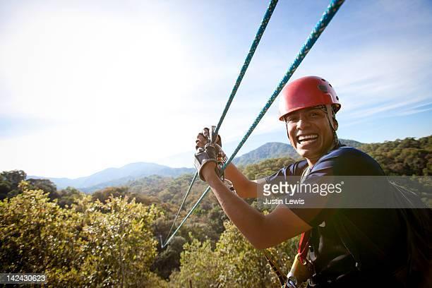 Guy smiling with hands on zip line over tree tops