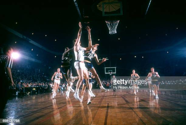 Guy Sparrow of the New York Knicks goes for the lay up as Lennie Rosenbluth and Woody Sauldsberry go for the block during an NBA game on November 3...