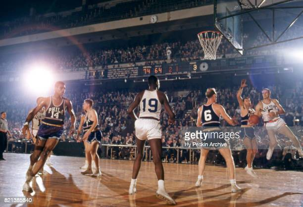 Guy Sparrow of the New York Knicks looks to pass as he is defended by Neil Johnston and Paul Arizin of the Philadelphia Warriors during an NBA game...