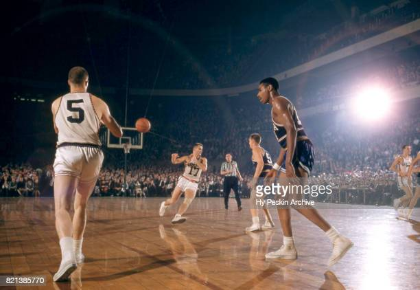 Guy Sparrow of the New York Knicks receives the pass from teammate Ron Sobie as they are defended by Woody Sauldsberry and George Dempsey of the...