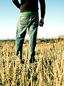 Guy standing in field with back facing camera.