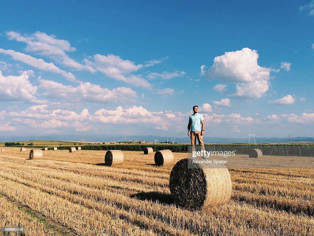 Guy standing on haystack in Transylvania, Romania