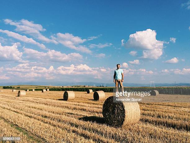 Guy standing on haystack in Transylvania, Romania