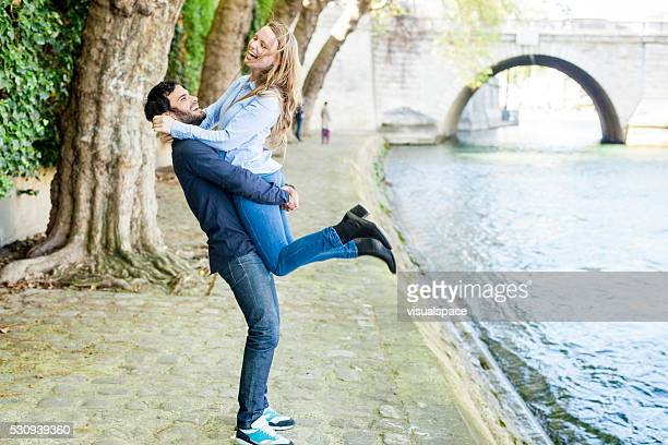 Guy Swaying His Girlfriend In The Air At The Riverbank