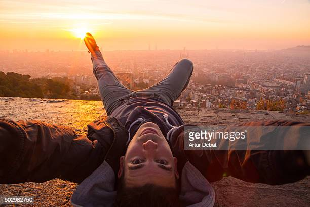 Guy taking a original selfie laying on the Barcelona bunkers (Turo de la Rovira) with the Barcelona cityscape on beautiful sunrise light.
