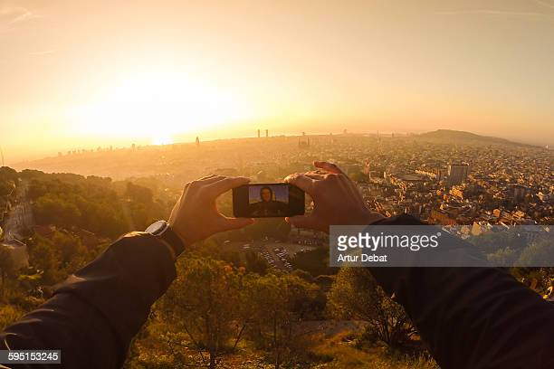 Guy taking a selfie from above Barcelona city.