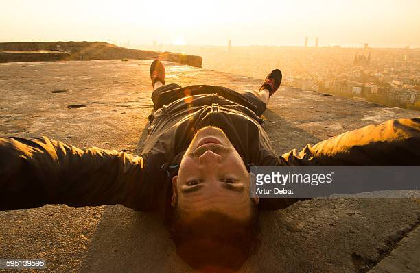 Guy taking a selfie laying from above Barcelona.