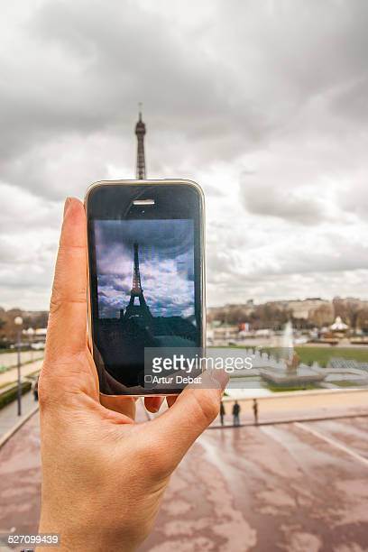 Guy taking picture of the Eiffel Tower in Paris with smartphone in first person view Pov
