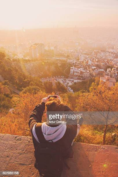 Guy taking pictures from the Barcelona bunkers (Turo de la Rovira) to the Barcelona cityscape on sunrise, solo traveller with a elevated viewpoint.