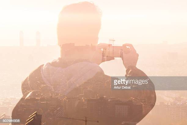 Guy taking pictures from the Barcelona bunkers (Turo de la Rovira) with the Barcelona cityscape on beautiful sunrise light.