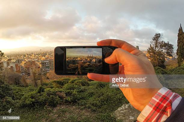 Guy taking pictures with his phone on Barcelona.