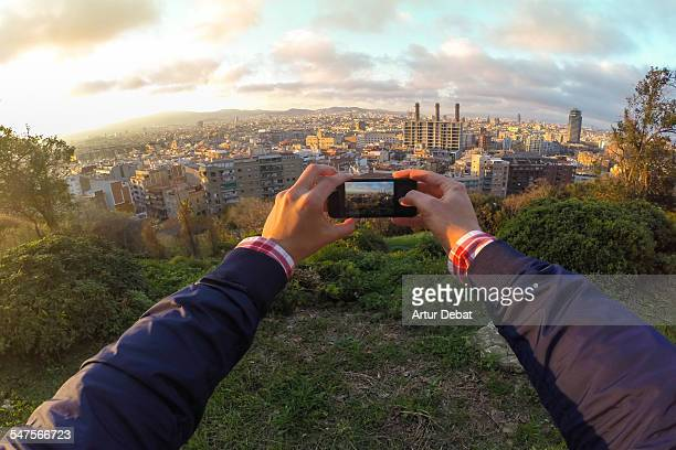 Guy taking pictures with phone on Barcelona city.