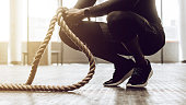 Close up of a man sitting on his toes holding a pair of battle ropes for workout. guy at the gym working out with fitness rope.