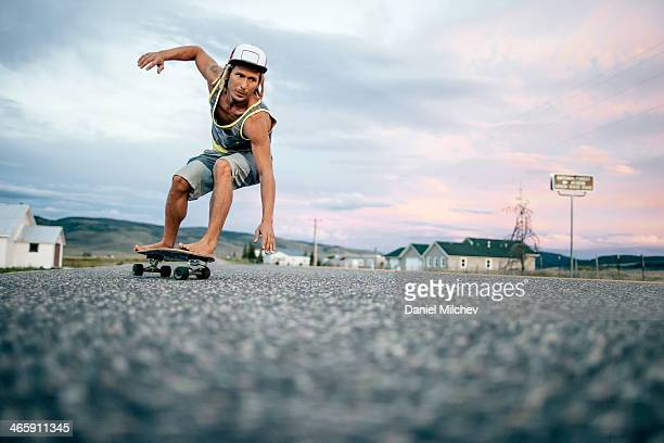 Guy turining on his skateboard at sunset.