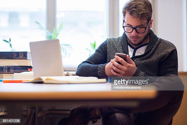 Guy using smartphone and laptop