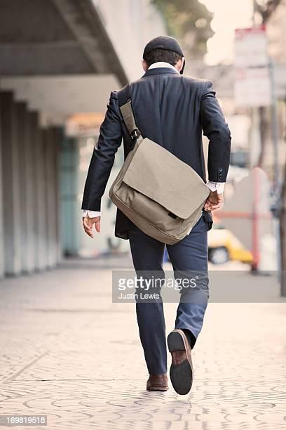 Guy walking down sidewalk with shoulder bag