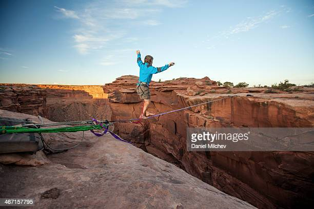 Guy walking on a line over a canyon in Moab.