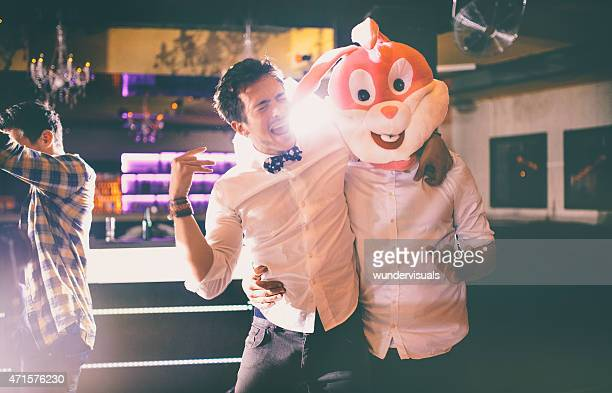 Guy wearing bunny head with friend at party in club