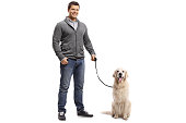 Full length portrait of a guy with a labrador retriever dog isolated on white background