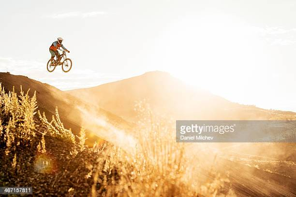 Guy with a mountain bike jumping in to the sun.