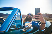 guy with beard taking selfie in vintage car of himself to show off.