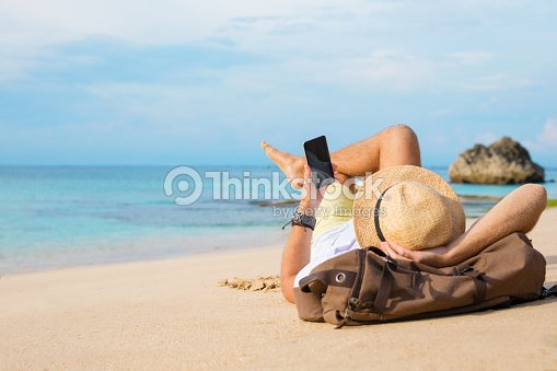 Guy with smartphone lying on the beach : Stock Photo