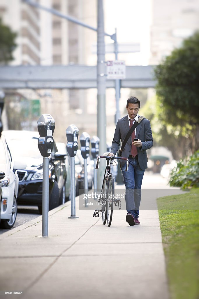 Guy working on phone with bike along city sidewalk : Stock Photo