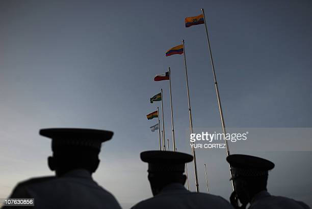 Guyanese policemen observe the sunset after the closing ceremony of the Union of South American Nations Summit on November 26 2010 in Georgetown...