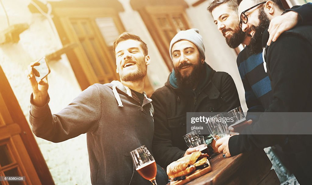 Guys at pub taking selfies. : Stock Photo