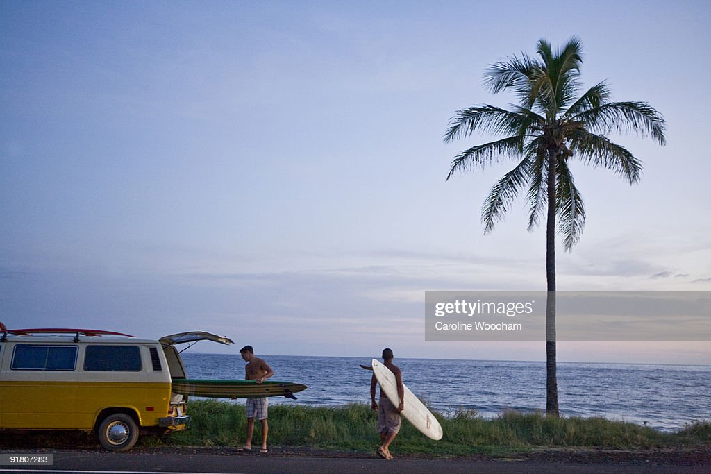 Guys going surfing at sunset. : Stock Photo