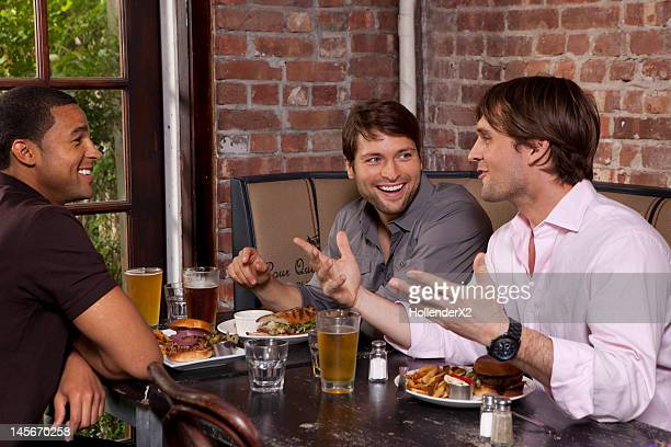guys hanging out over beers at dinner