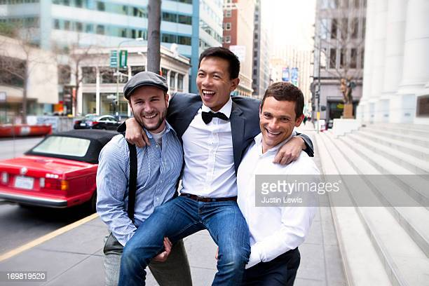 Guys laughing and carrying friend in city