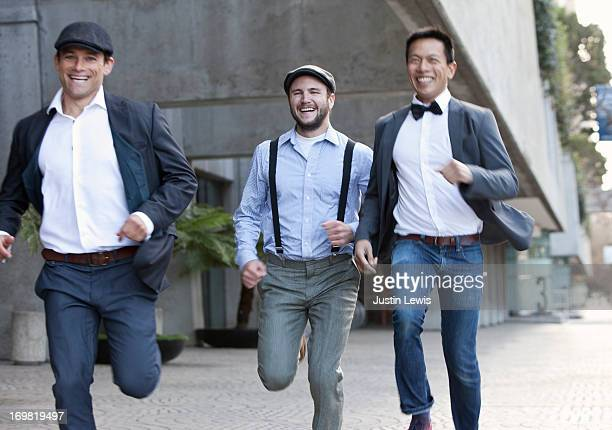 Guys laughing and running down the sidewalk