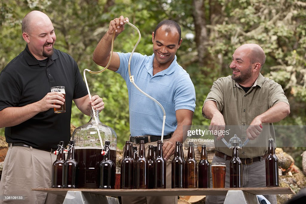 Guys making homebrewed beer. : Stock Photo
