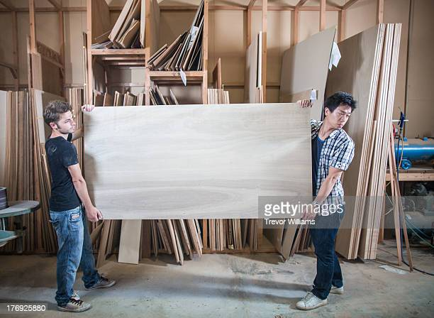 2 guys moving a piece of wood in a workshop