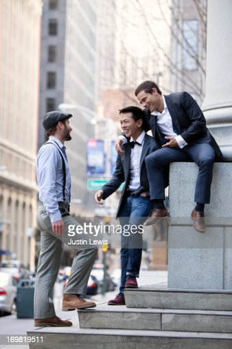 Guys on city steps laughing and hanging out