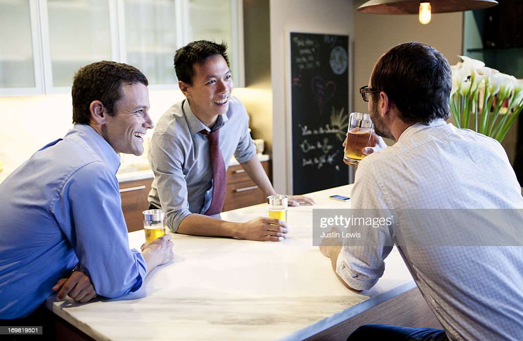 Guys smiling and drinking around marble island : Stock Photo