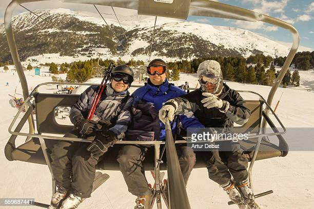 Guys taking selfie with stick on Andorra ski lift.