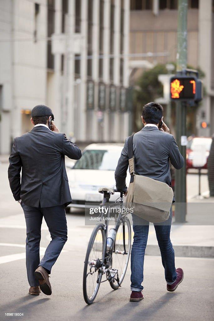 Guys walking across city street talking on phones : Stock Photo