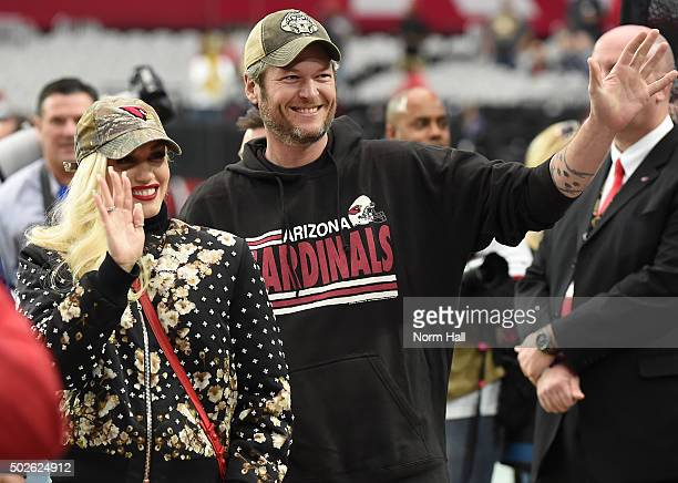 Gwen Stefani and Blake Shelton wave to fans prior to the NFL game between the Green Bay Packers and Arizona Cardinals at University of Phoenix...