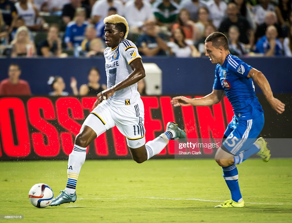 Gyasi Zardes #11 of Los Angeles Galaxy dribbles upfield as Donny Toia #25 of Montreal Impact chases during Los Angeles Galaxy's MLS match against Montreal Impact at the StubHub Center on September 12, 2015 in Carson, California. The match ended in 0-0 tie