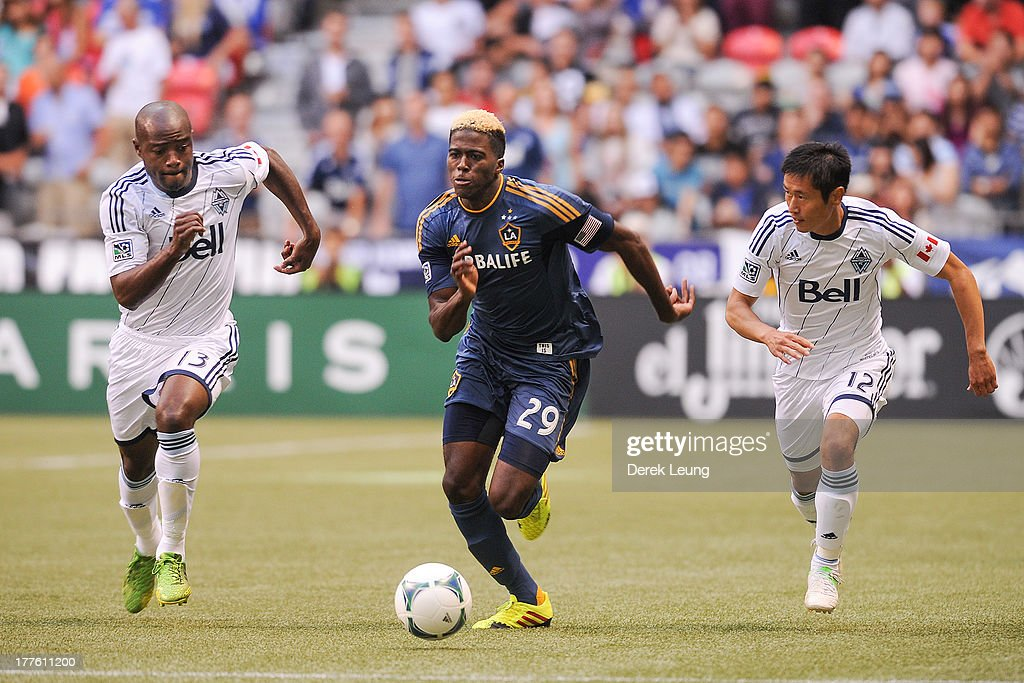 Gyasi Zardes of the Los Angeles Galaxy runs past the defence of Nigel ReoCoker and YoungPyo Lee of the Vancouver Whitecaps during an MLS match at BC...