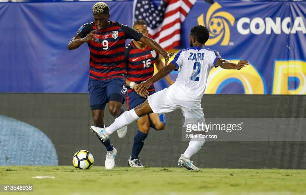 Gyasi Zardes of the United States dribbles past the defense of Nicolas Zaire of Martinique during the first half of the CONCACAF Group B match at...