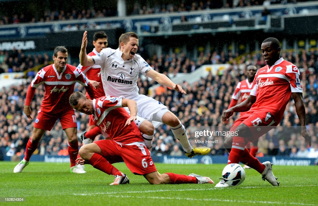 Gylfi Siggurdsson of Spurs is brought down by Clint Hill of QPR as he attempts to get a shot away during the Barclays Premier League match between Tottenham Hotspur and Queens Park Rangers at White Hart Lane on September 23, 2012 in London, England.